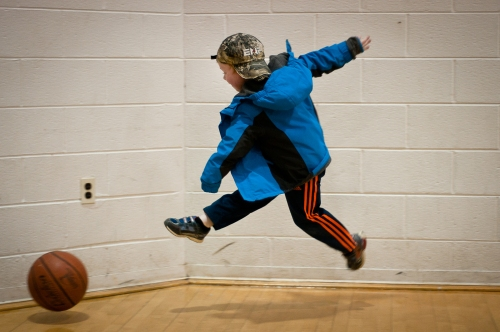 Boy kicking a basketball